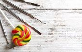 stock photo of lollipops  - Dentist tools with lollipop on wooden background - JPG