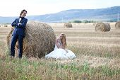 pic of hay bale  - Married couple having fun on a field with hay bales - JPG