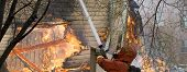 foto of firefighter  - Firefighter Fighting Fire in house with water - JPG