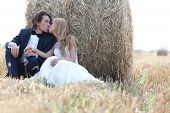 image of hay bale  - Young married couple kissing in a hay bale field - JPG