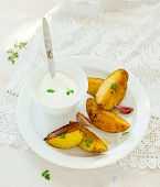 stock photo of baked potato  - Segments of baked potato and sauce on a white plate - JPG