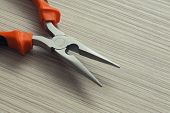 stock photo of extreme close-up  - pliers closeup on wooden background - JPG