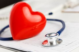 pic of stethoscope  - Medical stethoscope and red toy heart lying on cardiogram chart closeup - JPG