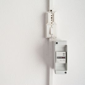 stock photo of electricity meter  - electricity meter in a white wall with copy space - JPG