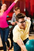 stock photo of bowling ball  - Group of friends in a bowling alley having fun - JPG