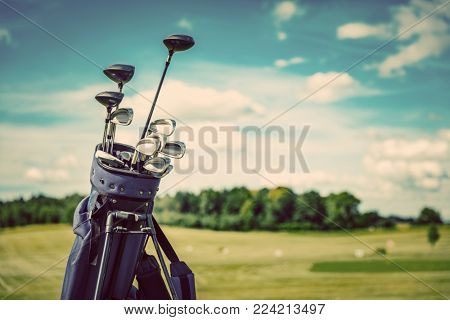 poster of Golf equipment bag standing on a course. Summer sport and activity. Golf clubs close-up.