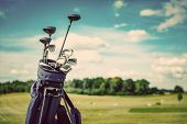 Golf equipment bag standing on a course. Summer sport and activity. Golf clubs close-up. poster
