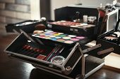 Case of professional makeup artist with cosmetic and tools on table indoors poster