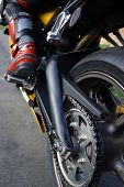 foto of peg-leg  - Image of rear motorcycle wheel and sproket showing chain guard rear swinging arm and riders left foot and lower leg