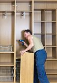 stock photo of assemblage  - The man is engaged in assemblage of a new wardrobe - JPG