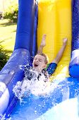 foto of young boy  - Young boy splashing water at bottom of water slide - JPG