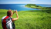 Young woman with backpack standing on a hill with green grass and making snapshot of a beautiful sce