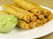 image of flauta  - A plate of chicken taquitos with a side of guacamole - JPG