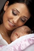 image of iranian  - Young Attractive Ethnic Woman Holding Her Newborn Baby Under Dramatic Lighting - JPG