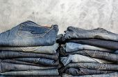 Carelessly Folded Jeans In Two Piles On A Gray Background. Close-up Of Jeans In Different Colors. Je poster
