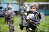 picture of paintball  - Boy in the camouflage holds a paintball gun barrel up in one hand and protective helmet in another - JPG