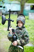 picture of bus-shelter  - Boy in the camouflage suit holds a paintball gun barrel up and says something - JPG
