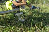 Cyclist Taking A Break With Bike Pedal In Foreground Sideways On Grass And The Person Visible Behind poster