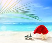 Christmas Holidays Concept. Santa Claus Hat And Christmas Ball On Summer Sand Beach. Palm Branch. poster