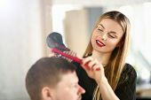 Young Girl Hairdresser Holding Dryer And Hairbrush. Woman Hairstylist Drying Male Hair In Beauty Sal poster