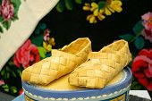 Old Russian Sandals Made Of Bark. Birch Bark Shoes, Traditional Old Russian Shoes Lie On An Old Trad poster