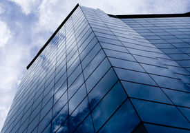 stock photo of commercial building  - the blue sky reflects in the glass of a skyscraper in singapore - JPG