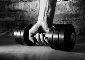 stock photo of barbell  - male hand is holding metal barbell against brick wall - JPG