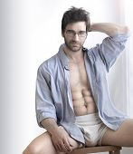 stock photo of six pack  - Playful sexy portrait of a handsome buff man in underwear and open business shirt with sensual expression against white - JPG