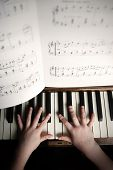 child's hands playing on a old piano