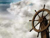 image of ship steering wheel  - Illustration of a ships wheel at an oblique angle on a cloudy day - JPG