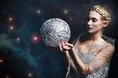 foto of starry  - Woman holding a silver bullet against the starry sky - JPG