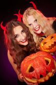 Portrait of two horned females showing carved Halloween pumpkins and looking at camera
