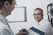 foto of button down shirt  - Doctor writing on medical chart with smiling patient - JPG