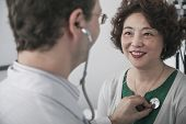 stock photo of medium-  length hair  - Doctor checking heartbeat of a patient with a stethoscope - JPG