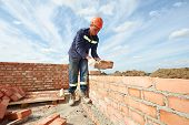 stock photo of trowel  - construction mason worker bricklayer installing red brick with trowel putty knife outdoors - JPG