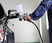 stock photo of air paint gun  - Mechanic painting the car in auto repair shop - JPG