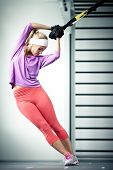 stock photo of muscle  - Young woman streching muscles TRX training - JPG