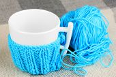 image of blue things  - Cup with knitted thing on it close up - JPG