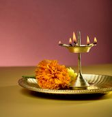 stock photo of pooja  - Indian lamp and marigold flower in a plate - JPG