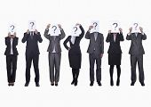 stock photo of anonymous  - Medium group of business people in a row holding up paper with question mark - JPG