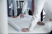 stock photo of blueprints  - Two architects discussing over a blueprint in the office - JPG