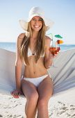 Smiling blonde wearing bikini and sunhat sitting on hammock with cocktail on the beach