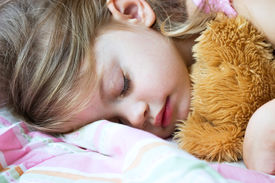 stock photo of goodnight  - Toddler sleeping with her teddy bear on a pink blanket - JPG