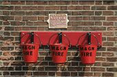 picture of olden days  - row of red fire buckets fixed on a brick wall at a railway museum used in the olden days   - JPG