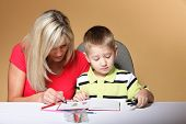 foto of daycare  - mother and son drawing together mom helping with homework daycare brown background