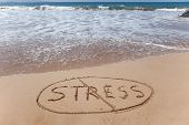 "image of handwriting  - ""Stress"" written in sand on a beautiful beach and then crossed out to symbolize stress relief. - JPG"