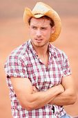 Cowboy man handsome and good looking with hat in rural USA countryside. Male model in american weste