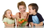 stock photo of healthy eating girl  - Woman feeding kids with fresh vegetables  - JPG