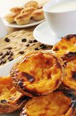 closeup of some pasteis de nata and some pasteis de feijao, typical Portuguese pastries, on a set ta