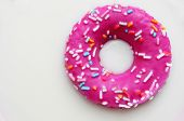 foto of milk  - a donut coated with a pink frosting and sprinkles of different colors soaking in milk - JPG